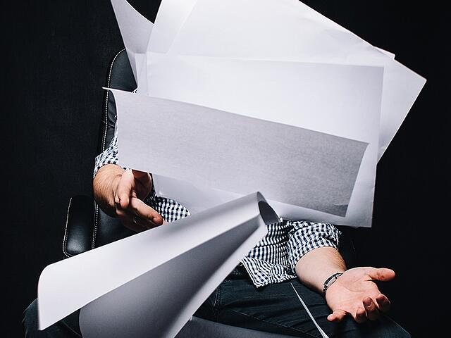 Man angrily throwing business papers during resignation